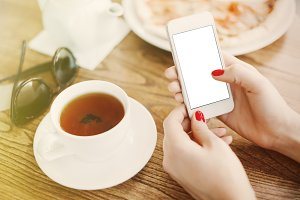 Girl holding smartphone with empty screen at cafe