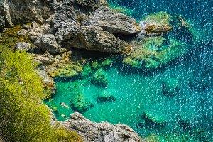 Tourists shorkling between Rocks in Azure Bay of Beautiful Paleokastritsa in Corfu Island, Greece