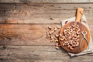 Roasted cashew nuts with salt on cutting board over textured wooden background