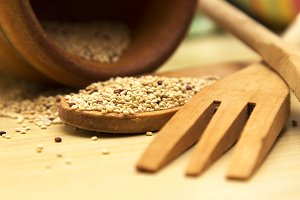 Spoon and wooden fork with quinoa on wooden table