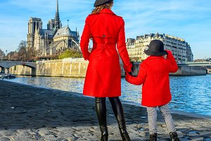 mother and child travellers standing on embankment in Paris