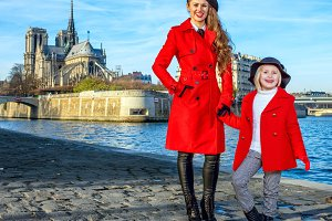 mother and daughter tourists standing on embankment in Paris