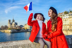 stylish mother and child travellers in Paris, France rising flag