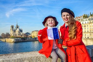 Portrait of mother and child tourists in Paris with French flag