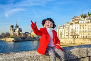 child on embankment near Notre Dame de Paris in Paris, France