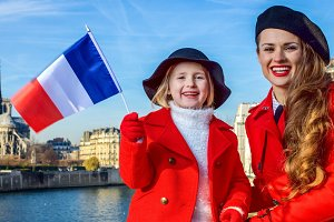 mother and daughter travellers in Paris, France showing flag