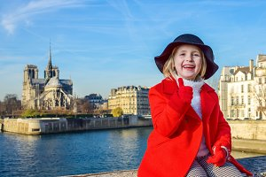 smiling child on embankment in Paris, France showing thumbs up