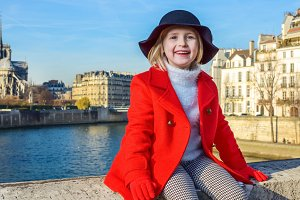 happy modern child on embankment in Paris, France relaxing