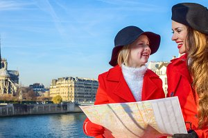 trendy mother and daughter travellers in Paris, France with map