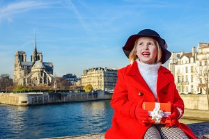 girl with Christmas present box looking into distance in Paris