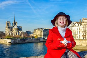 happy child on embankment in Paris, France with Christmas gift