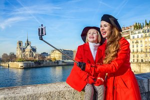mother and child tourists on embankment in Paris taking selfie