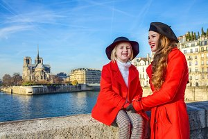 mother and daughter travellers on embankment in Paris, France