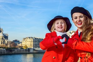 stylish mother and daughter in Paris showing heart shaped hands