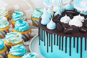 Festive cupcakes and cake with cream in blue on a white wooden background