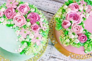 Two celebratory cake with flowers rose on a white wooden background