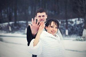 Happy wedding couple raises rings