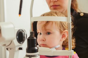 Child's optometry - little girl hecks eyesight in eye ophthalmological clinic