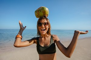 Happy woman balancing a coconut