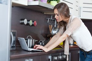 Woman with computer in the kitchen