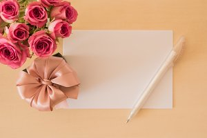 Present, card, pen and pink roses