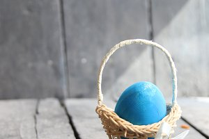 Easter egg in a basket on a vintage background