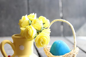 Easter egg in a basket on a vintage background And spring flowers