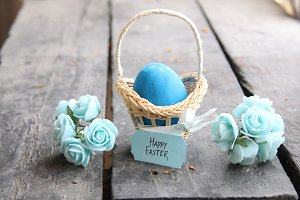 Happy easter. Easter egg in a basket on a vintage background and spring flowers..