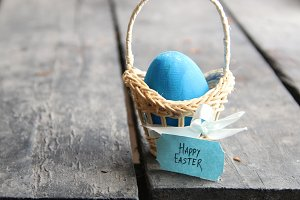 Happy easter. Blue egg on rustic table and a basket with a tag.