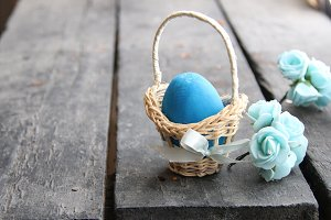 Easter background. Blue egg in basket on rustic table