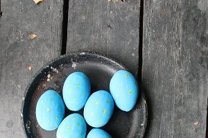Easter eggs in a frying pan on a vintage wooden background