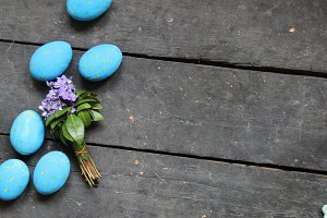 Easter eggs and spring flowers on wooden background