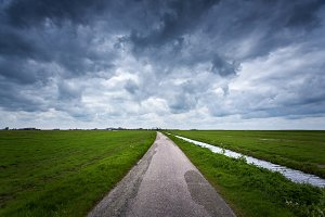 Road with dramatic blue cloudy sky
