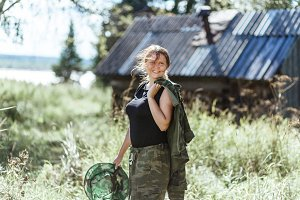 Young beautiful country woman in camouflage outfit discovering nature in the forest village with mosquito net. Travel lifestyle concept