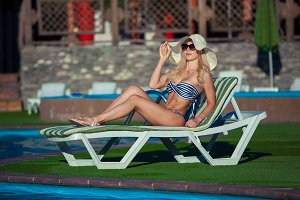Beautiful girl is sunbathing in swimsuit with pleasure. She is lying near a swimming pool. The lady is enjoying the sun and smiling. She is wearing sunglasses and a hat