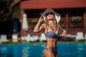 Beautiful woman swimming pool summer vacation summertiA beautiful young woman in swimwear at the poolside is standing straight. She is in a pretty hat and black sunglasses.