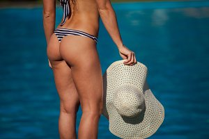 It is close up fashion image of gorgeous woman with perfect body and butt holding hat, posing near luxury pool wearing pretty bikini.