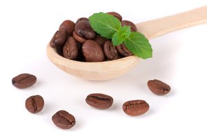 Coffee beans in a wooden spoon with leaf isolated on a white background