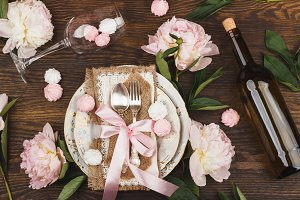 Tableware and silverware with puffy light pink peonies on the wooden background
