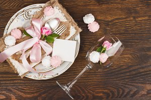 Tableware and silverware with puffy light pink roses on the wooden background
