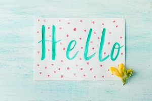 Hello word spelling by watercolor hand lettering yellow flowers
