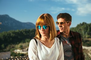 Young man and woman posing in sunglasses