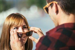 Man putting sunglasses off woman