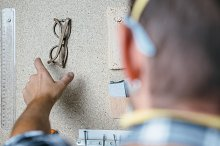 Man taking glasses off wall