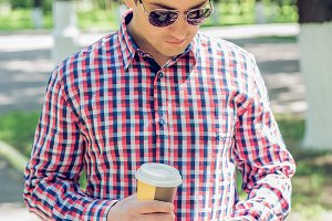 A man in a shirt and jeans and sunglasses, holding a mobile phone coffee or tea, read the conversation messages on your phone, the concept of summer, a businessman on vacation. City lifestyle. On the street in the park