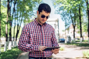 The man in the summer in the park, reading glasses, looking a map and news feed on social networks, watching  video film in jeans bright sunny day. Idea concept businessman city plan. Lifestyle, I get directions  the cards.
