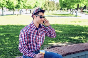 man in  shirt and jeans  glasses, talking on the phone,  smartphone, the concept of summer,  businessman  vacation. City lifestyle.  the street in the park.