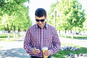 The man in the summer in the park, reading a message on your phone, glasses, watching the map and news feed  social networks, happy smiles   video film in jeans bright sunny day. Idea concept businessman city plan. Lifestyle, I get directions  the cards.