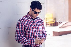man in  shirt and jeans  sunglasses, holding  mobile phone, read the conversation messages on your , the concept of summer,  businessman  vacation. City lifestyle.