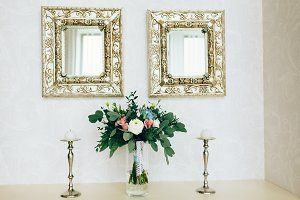 Beautiful bouquet between candlesticks and mirrors